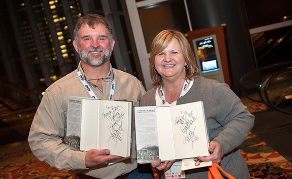 two people with signed copies of Keni Thomas's book